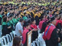 מקבלי תואר מוסמך באוניברסיטה לבושים בגלימה אקדמית בטקס הענקת התואר. למצולמים אין קשר לכתבה. צילום: אלמוג